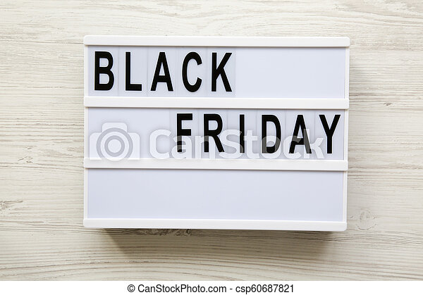 Top view, 'Black Friday' word on modern board over white wooden surface. Flat lay, overhead, from above. - csp60687821