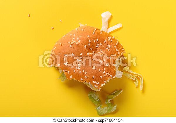 top view half eaten hamburger on a yellow background - csp71004154