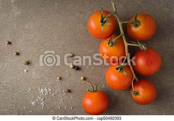 Top view of a bunch of natural cherry tomatoes on cement background with copy space - csp50492393