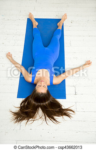 top view of a woman in corpse pose white studio top view