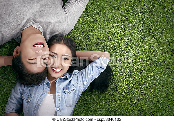 Top view of asian couple in love lying on a green grass at... stock ...