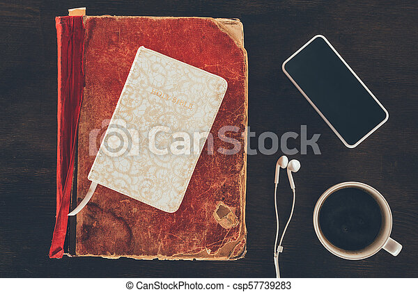 top view of bible with smartphone and cup on wooden table - csp57739283