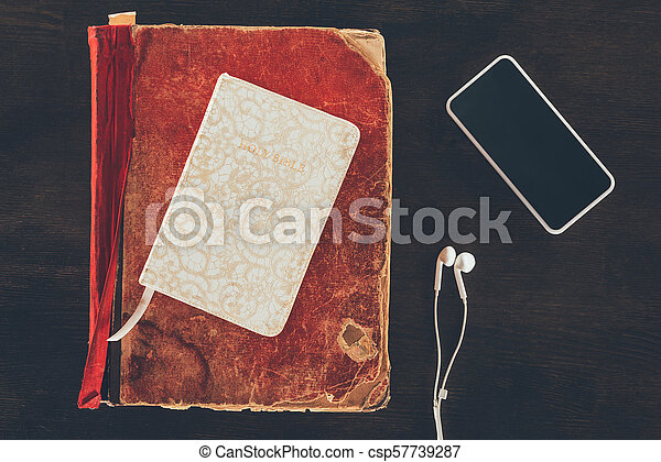 top view of bible with smartphone and earphones on wooden table - csp57739287