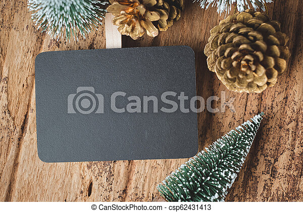 Top view of blank blackboard with xmas tree and gold pine cone on grunge wood table .winter holiday greeting card. space for display of design or content. - csp62431413