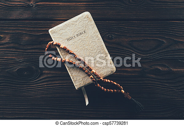 top view of closed holy bible and rosary with cross on wooden table - csp57739281
