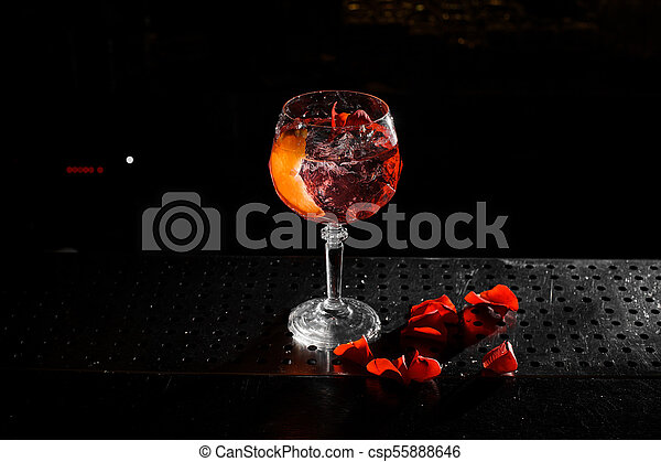 Top view of elegant glass filled with a fresh and tasty Aperol syringe summer cocktail on the black background - csp55888646