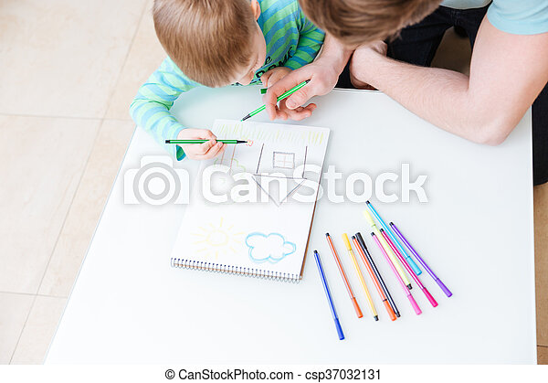 Top view of father and son drawing house together - csp37032131
