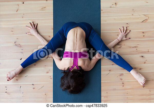 Top View Of Female Yogi Doing Advanced Kurmasana Tortoise Pose On Mat Indoors While Practicing Yoga