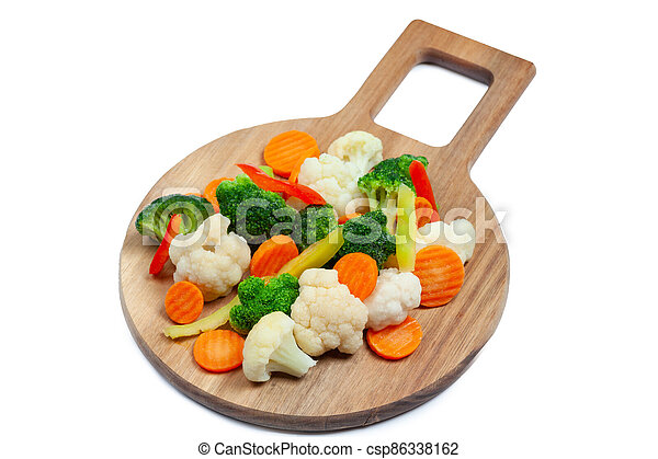 Top view of frozen mixed vegetables cauliflower, carrots, broccoli, sliced bell peppers lying on wooden cutting board - csp86338162