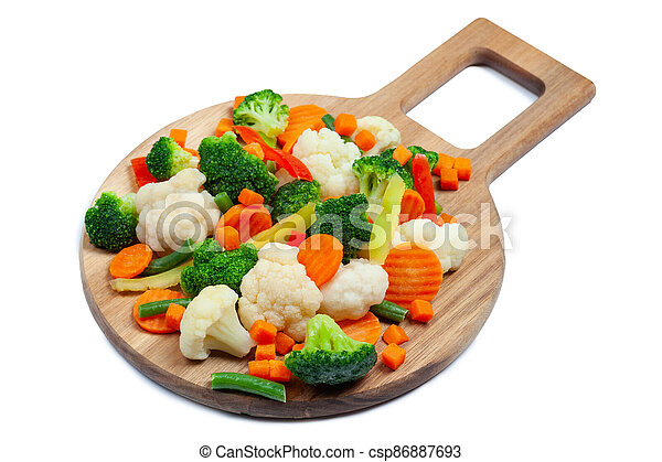 Top view of frozen mixed vegetables cauliflower, carrots, broccoli, sliced bell peppers lying on wooden cutting board - csp86887693