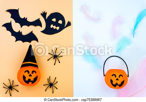 Top view of Halloween decoration, jack o lantern, ghost, bat and spider on yellow and white background with copy space for text. halloween concept. - csp75388987