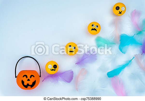 Top view of Halloween decoration, jack o lantern, ghost, bat and colorful feather on white background with copy space for text. halloween concept. - csp75388990