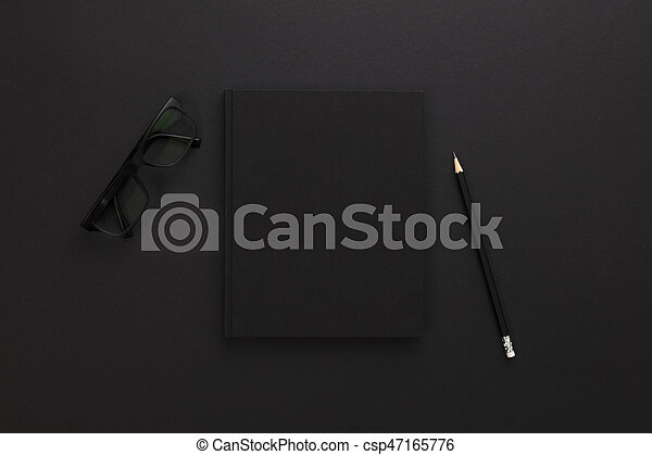 Top view of low key black office desk with notebook and supplies - csp47165776
