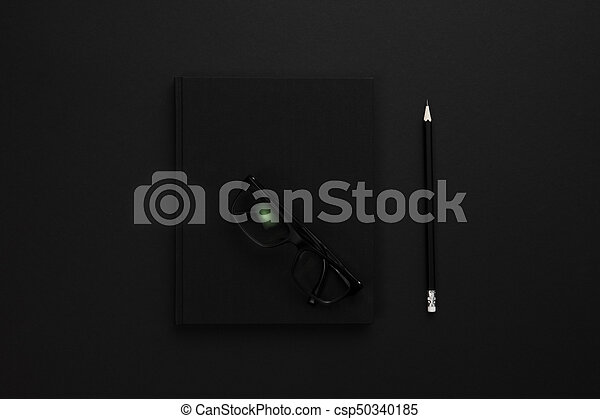 Top view of low key black office desk with notebook and supplies - csp50340185