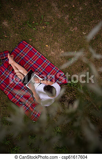 top view of man using a laptop computer under the tree - csp61617604