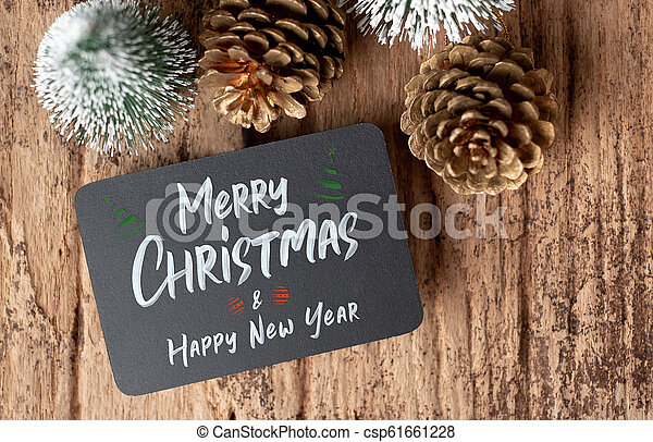 Top view of Merry Christmas and happy new year on blackboard with xmas tree and gold pine cone on grunge wood table .winter holiday greeting card. - csp61661228