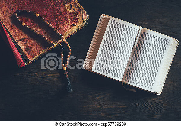 top view of open holy bible with rosary on table - csp57739289