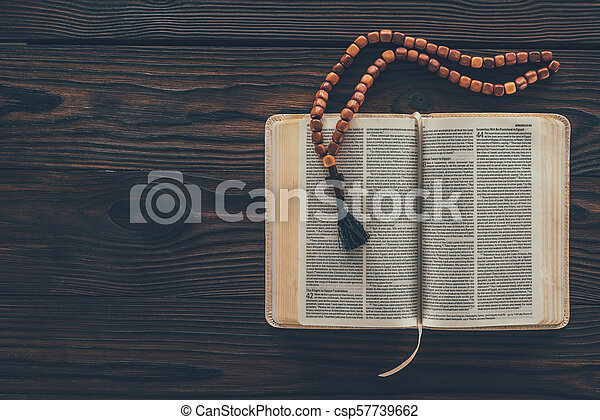 top view of open holy bible with rosary on wooden table - csp57739662