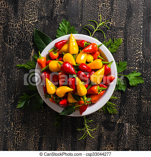 top view of plate with orange, red and yellow hot chili peppers, greenery on cracks black background, close up - csp33044277