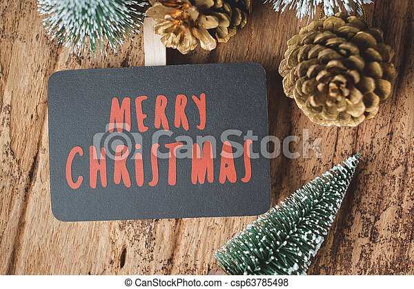 Top view of red Merry Christmas blackboard with xmas tree and gold pine cone on grunge wood table .winter holiday greeting card. - csp63785498