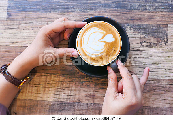 top view of women hand holding a coffee cup - csp86487179