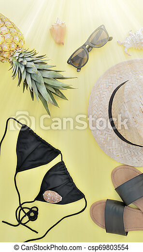 top view on beach accessories with pineapple on yellow background and sunlight effect - csp69803554