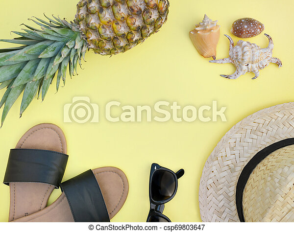 top view on beach accessories with pineapple on yellow background- summer vacation - csp69803647