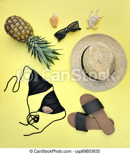 top view on beach accessories with pineapple on yellow background- summer vacation concept - csp69803635