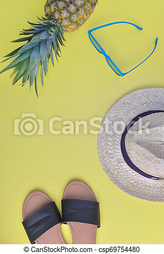 top view on female sandale straw hat, sunglasses and pineapple on yellow background - csp69754480
