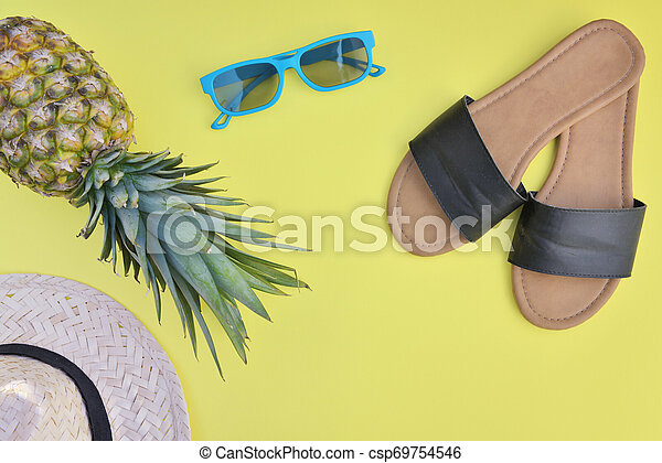 top view on female sandale straw hat, sunglasses and pineapple on yellow background - csp69754546