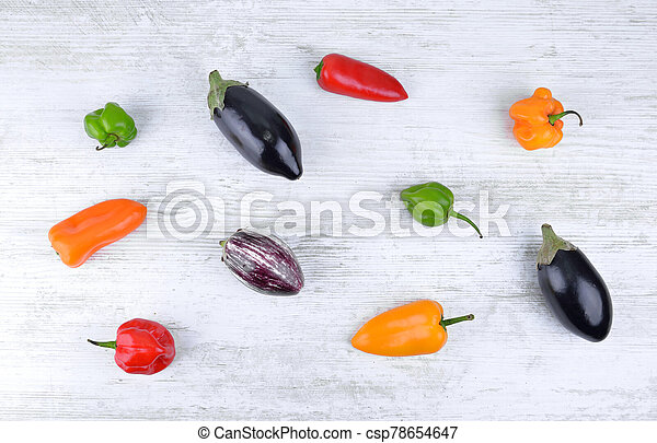 top view on hot colorful peppers and small eggplant on white table - csp78654647