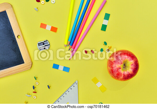 top view on suplies of school and red apple on yellow background - csp70181462