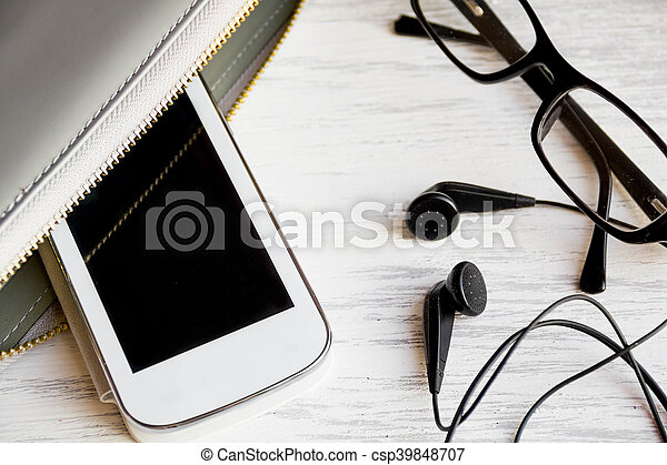 top view on things women bag. image smartphone with blank screen, headphones, room for text. overhead of office Desk, glasses, clutch, copy space - csp39848707