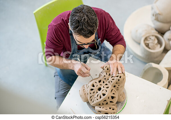 Topview of Ceramist Dressed in an Apron Sculpting Statue from Raw Clay in Bright Ceramic Workshop. - csp56215354