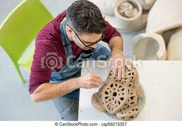 Topview of Ceramist Dressed in an Apron Sculpting Statue from Raw Clay in Bright Ceramic Workshop. - csp56215357