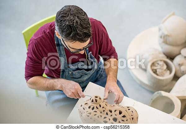 Topview of Ceramist Dressed in an Apron Sculpting Statue from Raw Clay in Bright Ceramic Workshop. - csp56215358