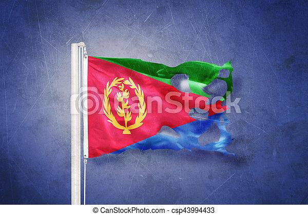 Torn flag of Eritrea flying against grunge background - csp43994433