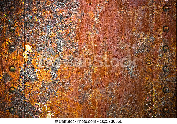 Torn rusty metal texture with rivets over red background - csp5730560