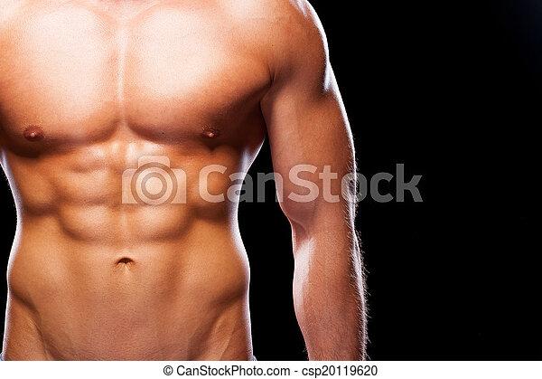Parece ideal. El primer plano de un joven musculoso con el torso perfecto parado contra el fondo negro - csp20119620