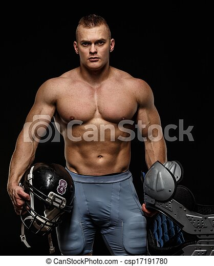 Hombre con torso musculoso desnudo sosteniendo accesorios de jugadores de fútbol americano - csp17191780