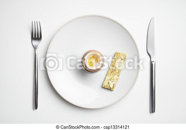 Huevo hervido y soldados tostadas en el plato con cuchillo y tenedor - csp13314121