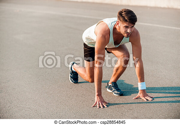 Total concentration. Confident young muscular man standing in starting line and looking forward - csp28854845