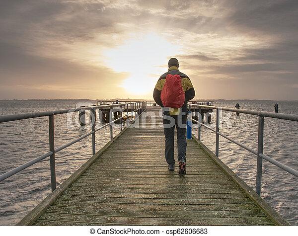 Tourist walk on wooden pier to the sea. Wooden bridge pier - csp62606683