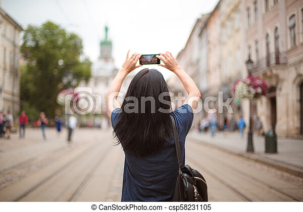 Tourist walking through the city center and taking photo on the smartphone - csp58231105