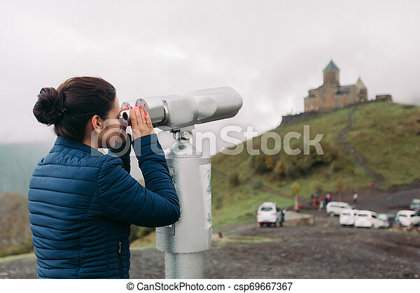 tourist woman looking at binoculars on a hillside - csp69667367