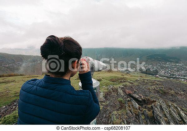 tourist woman looking at binoculars on a hillside - csp68208107