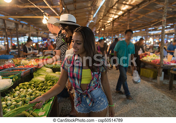 Tourists Choosing Vegetables On Traditional Asian Market Young People  Buying Products In Bazaar