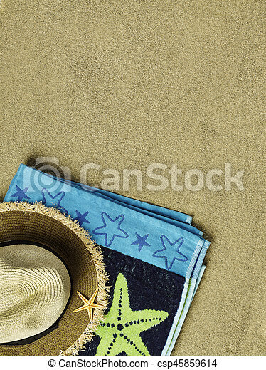 Towel and sun hat on sand
