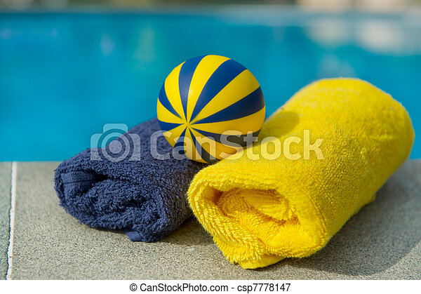 Towels and toys near the swimming pool. Towels and toys in blue and ...
