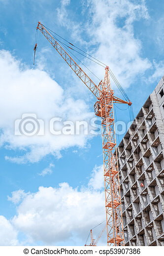 Tower crane on the construction site beneath blue cloudy sky - csp53907386